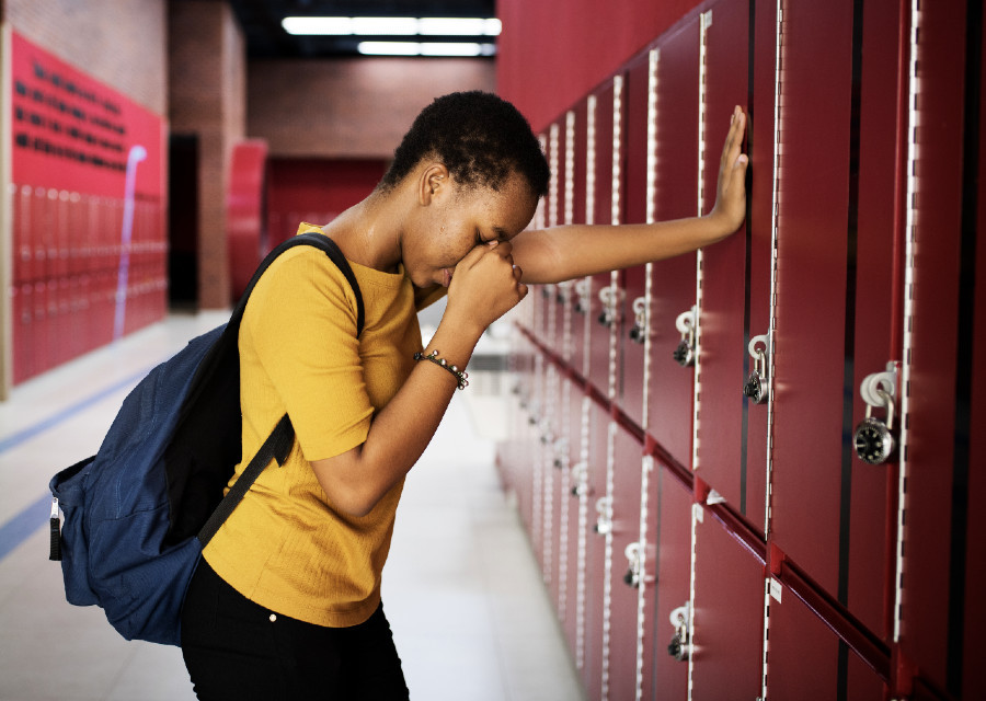 Sad girl by her locker weeping - collective and communal grief