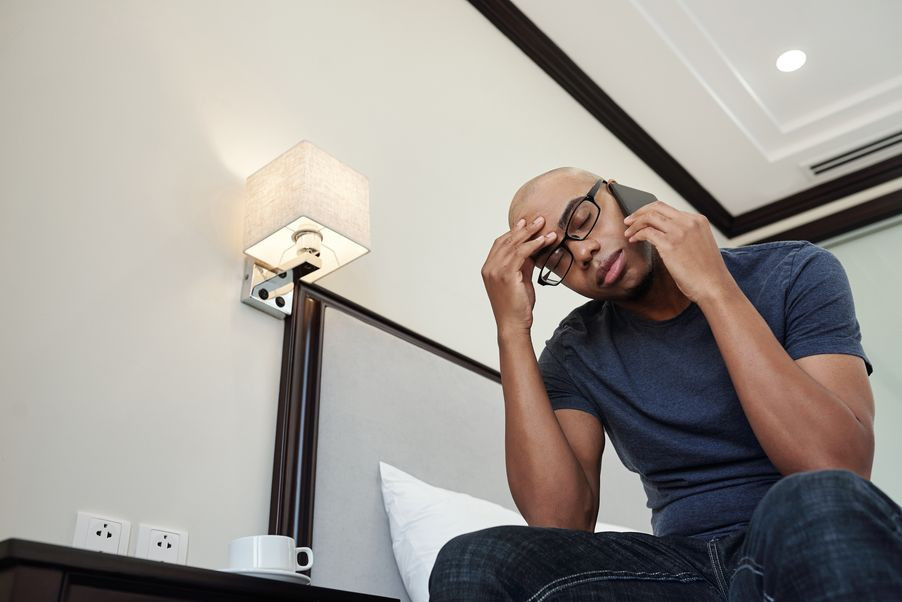 ired young Black man suffering from headache talking on phone with relative, friend or colleague| Balanced Wheel | How to reach out to somone grieving blog post