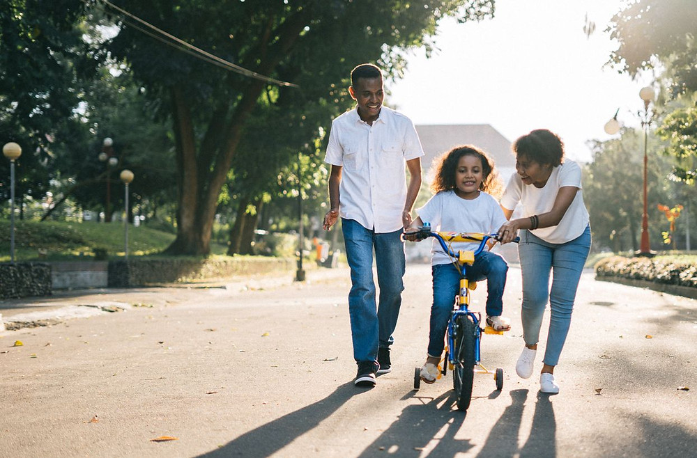 Happy young family with a todler on a bicycle