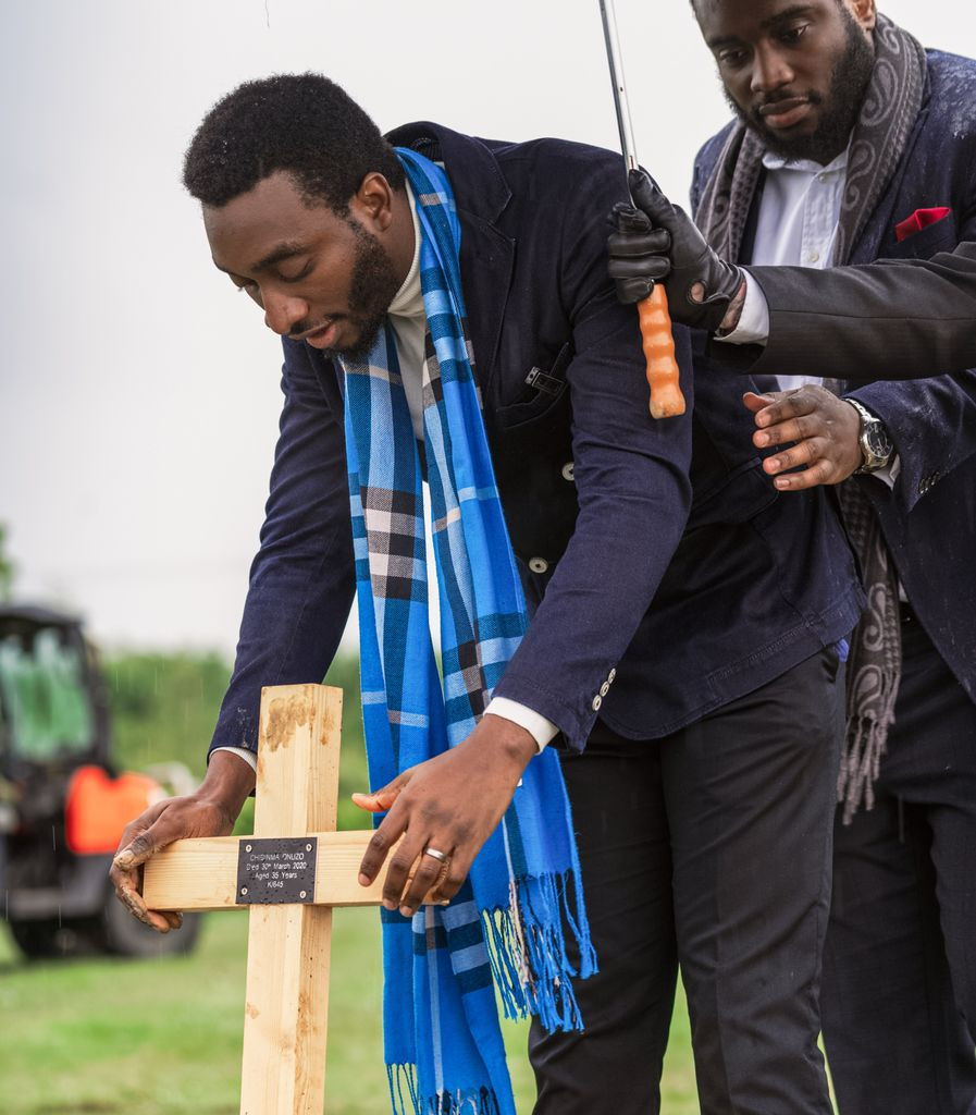 Tolulope Olajide pushing the cross into the soil at the head of Chidinma Olajide's grave