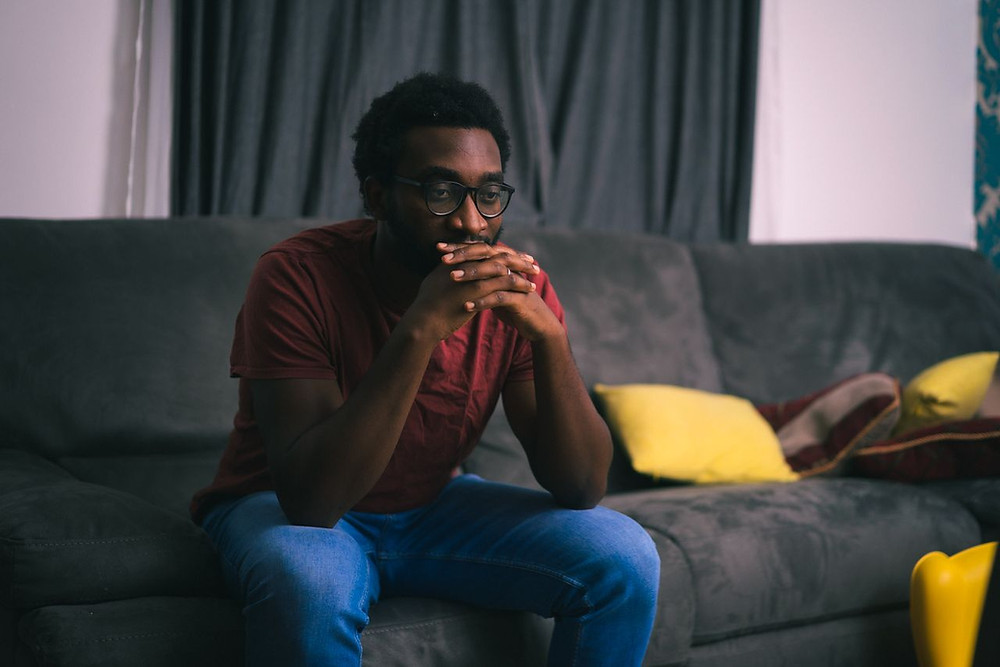 Tolulope Olajide seats on sofa in a reflective pose with both hands resting on his lips. Friend, How are You Mourning and Grieving the Death of Your Loved One?  | Balanced Wheel
