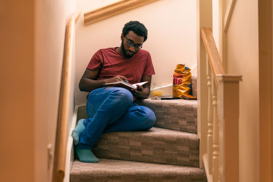 Tolulope Michael Olajide sat on the stairs writing into his journal | Balanced Wheel | How to reach out to somone grieving blog post