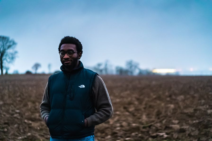 Tolulope Olajide standing in the middle of a farm that has recently been prepared for planting   Time Heals All Wounds, Does It?   Balanced Wheel