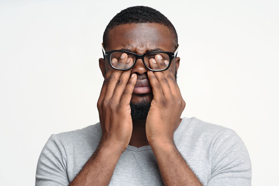 Tired eyes concept. Black man in glasses rubbing his eyes, white studio background | After the funeral, why do we stop reaching out to someone grieving | Balanced Wheel