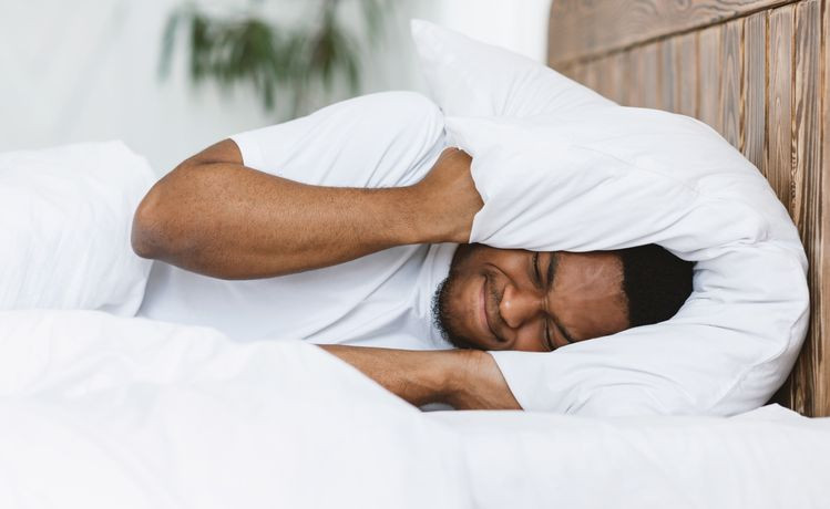 Disturbed Black Man Covering Ears With Pillow Suffering From Insomnia Lying In Bed At Home. Sleeplessness | Balanced Wheel