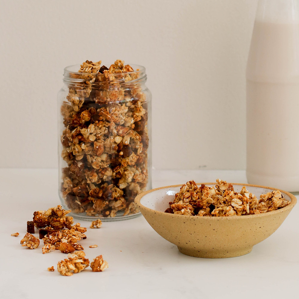 Granola in a jar and serving suggestion in a bowl with almond milk