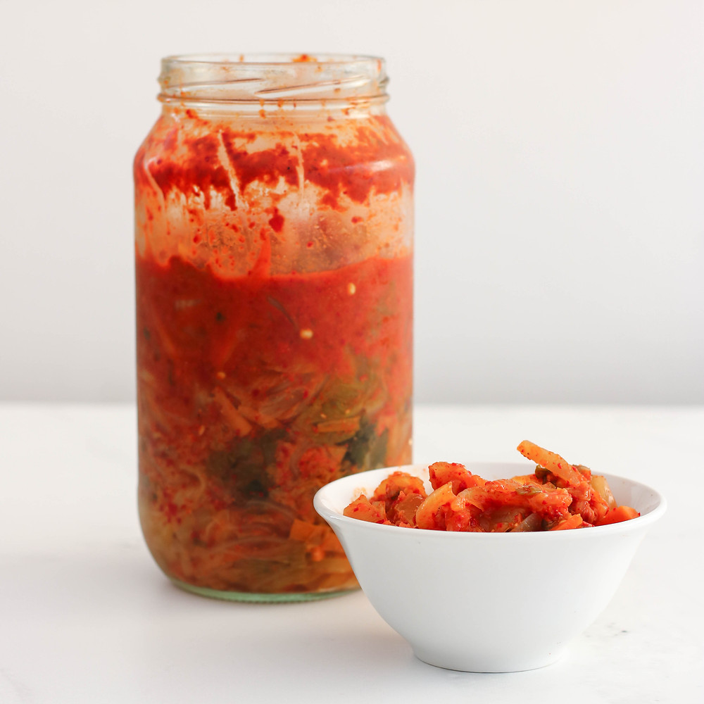 Glass jar of homemade Kimchi with a small bowl with Kimchi