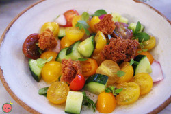 Salad of cherry tomatoes, cucumbers, fried sourdough, and red onion