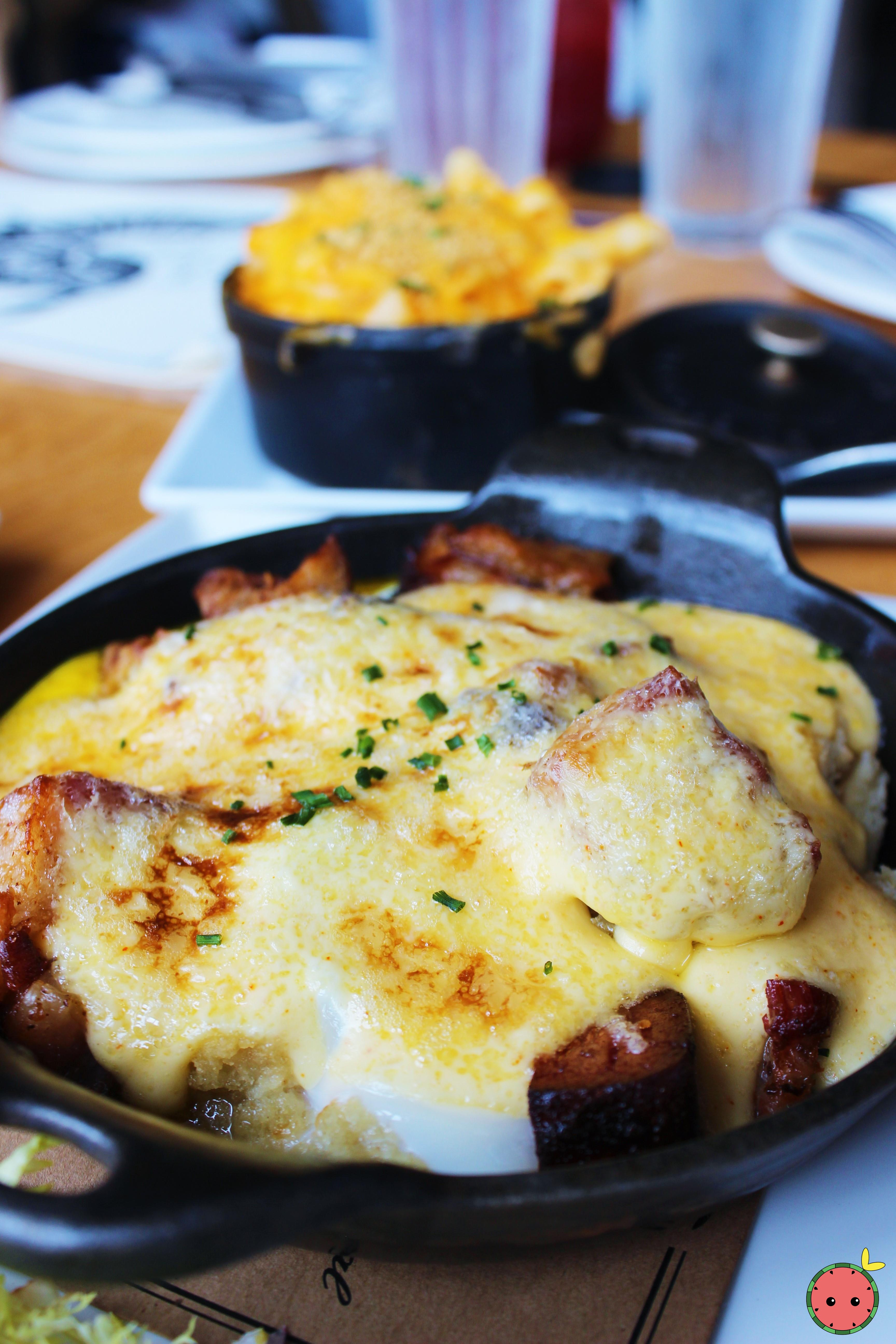 BLT benedict cast iron casserole with buttermilk biscuit crumble, soft poached egg, house-cured baco