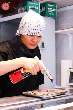 Sushi chef blow torching the wagyu