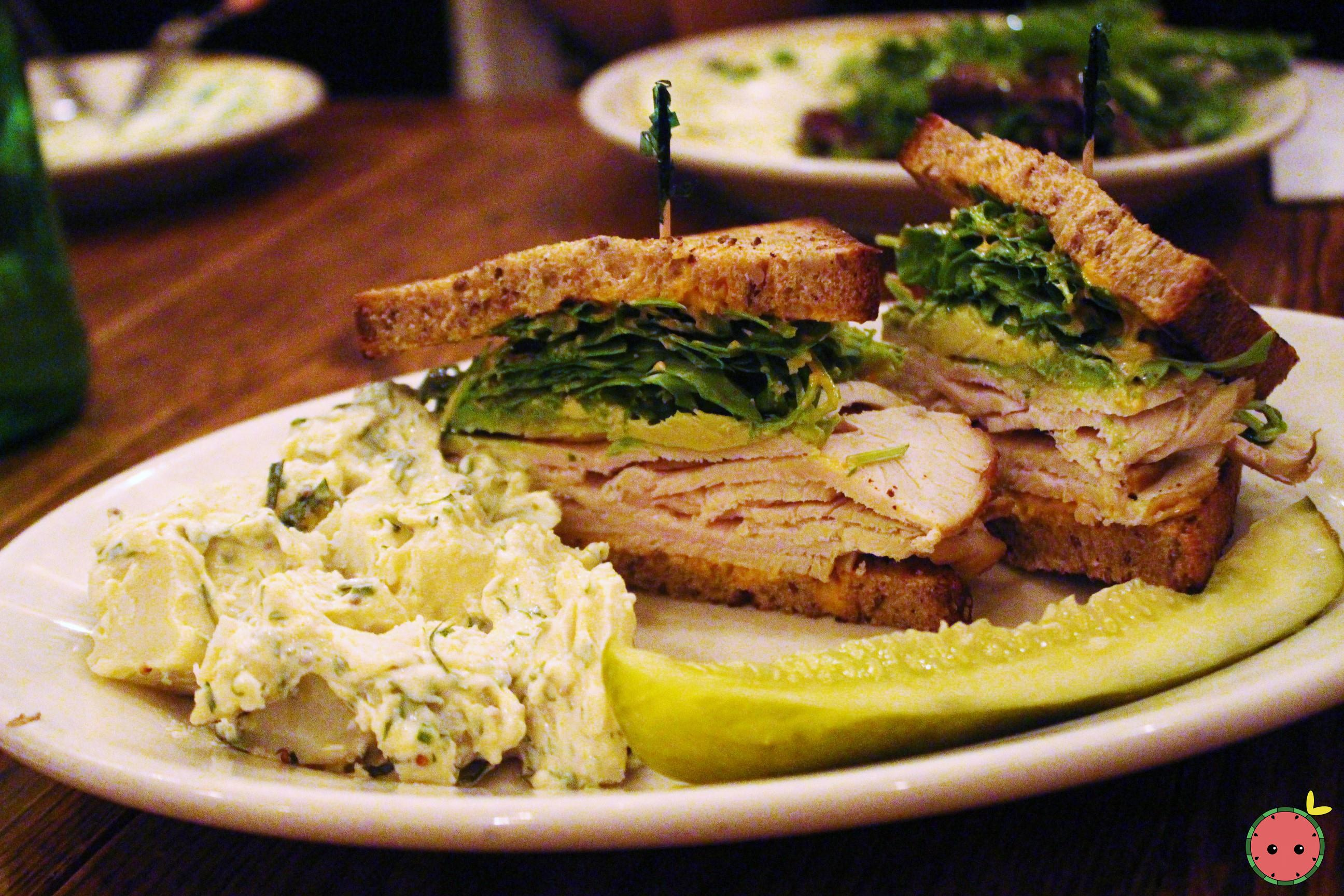 Turkey sandwich with argula, avocado, and spicy mayonnaise with side potato salad and pickle