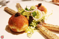 Soft boiled eggs rolled in breadcrumbs with truffled butter toasts