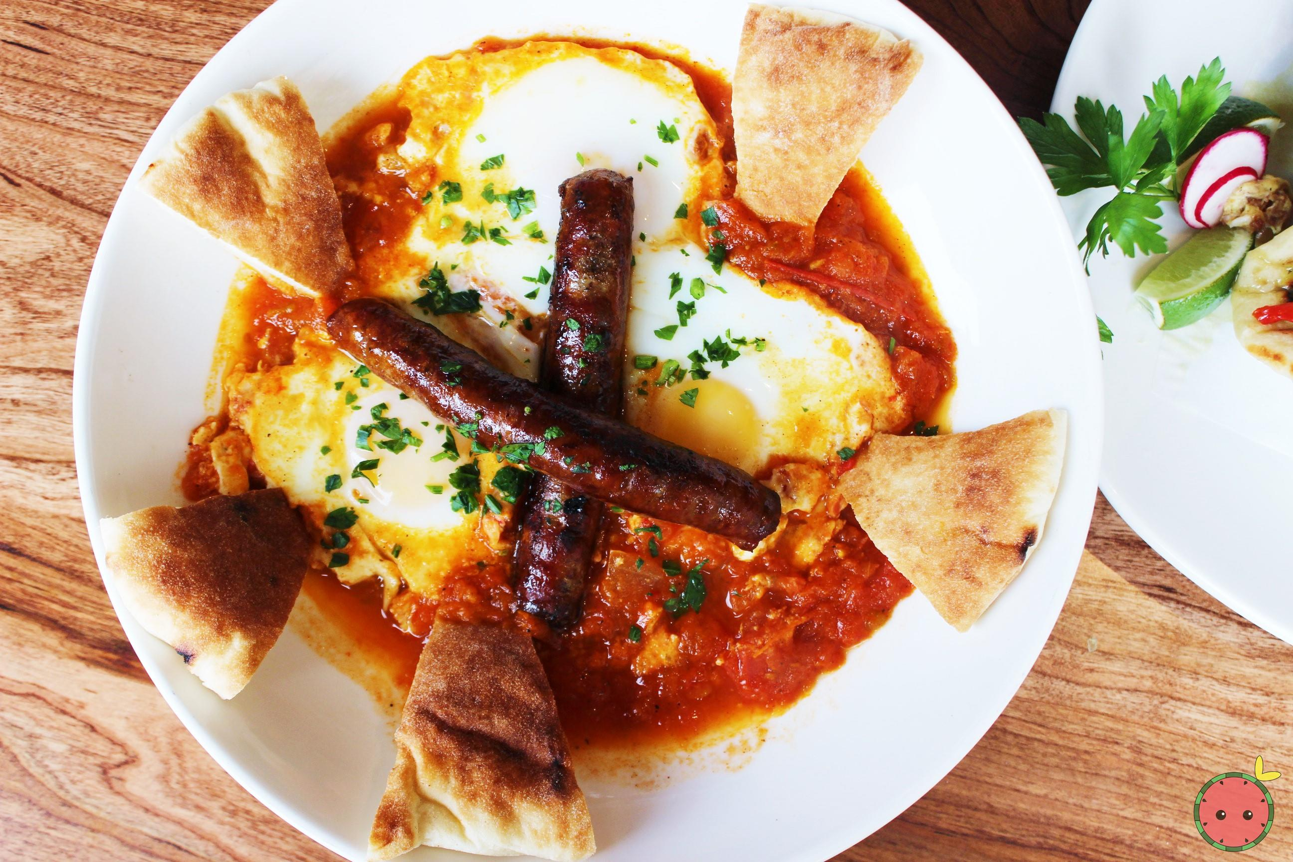 Shakshuka Moroccan Breakfast - Three eggs baked with tomato, onion, pepper, spices, tahini, pita, an