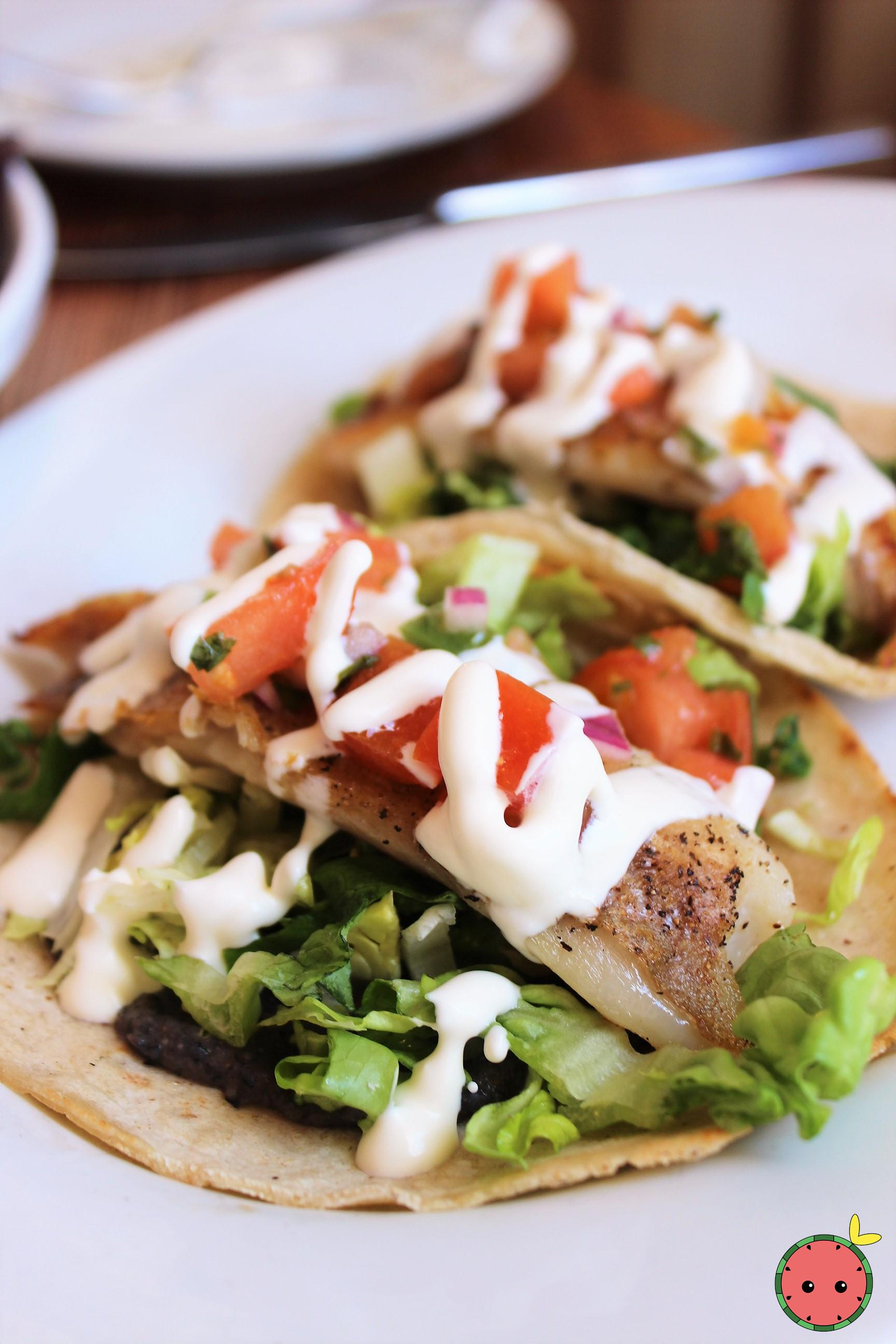 Seared Fish Taco with black bean sauce, lettuce, pico, avocado, and crema