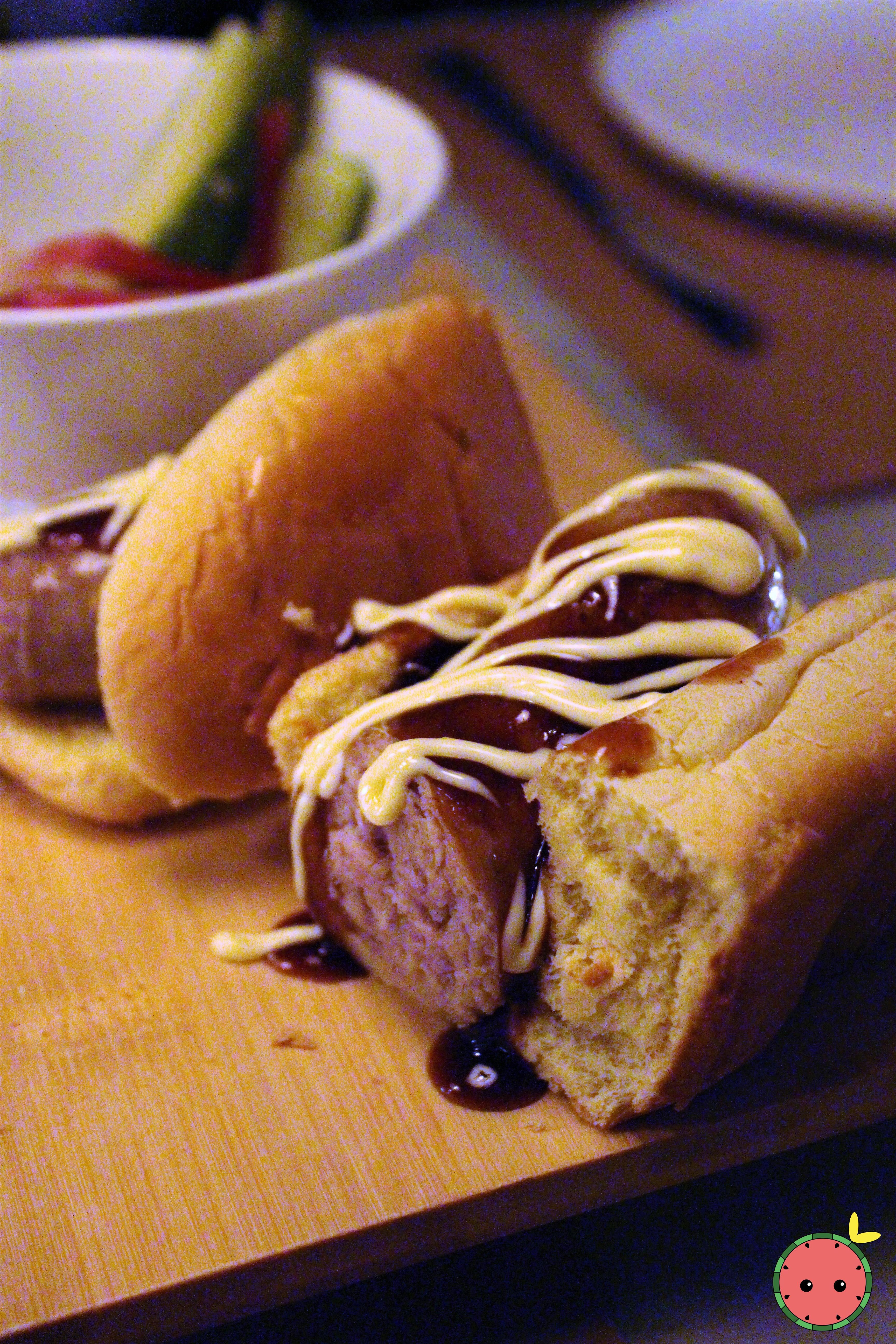 Dinnertable Dog with House Pickles - House miso sausage, potato bun, wasabi pea salt, sauces, and ma