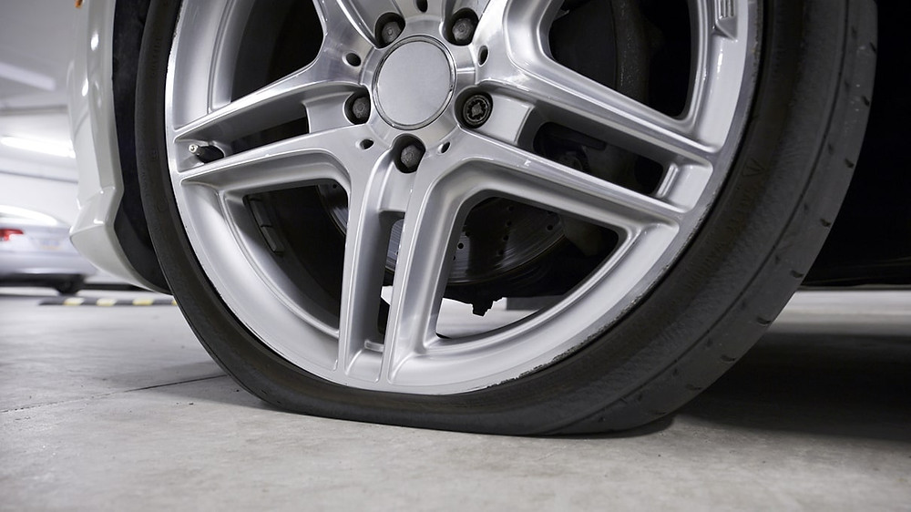 close-up of parked car with a flat tire