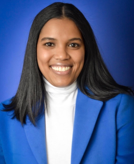 Black woman smiling in a blue blazer, white top, with a blue background.