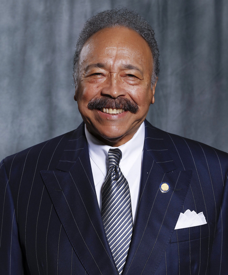 Black man smiling in a striped suit, with a grey background.