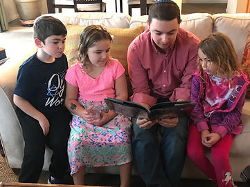 Student rabbi reading a book to our young Sunday school members