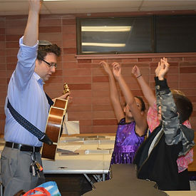 our student rabbi with his guitar playing music with some congregants