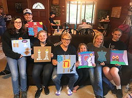 seven congregants and our student rabbi holding art work they made at a retreat up in the mountains,