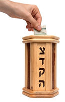 A wooden tzedakah box with someone putting money in it