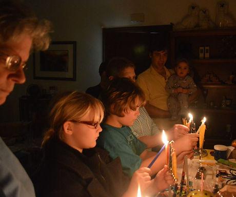 young congregants lighting their menorahs in a darkened room