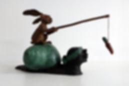 Brons beeld Anouk de Groot Slak met een vissende haas met een wortel