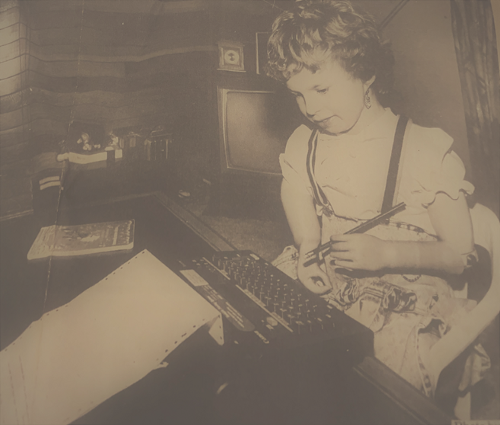 Me typing on a typewriter with my myoelectric arms holding an upside down pencil
