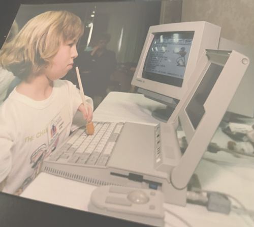 Me as a youngster typing on a computer with an upside down pencil that has a large grip on the end of it