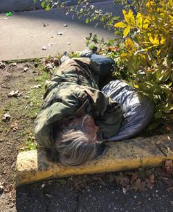 Man sleeping head on curb.jpg