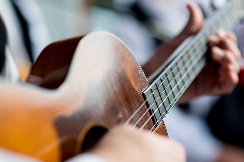 Close-up of man playing acoustic guitar.