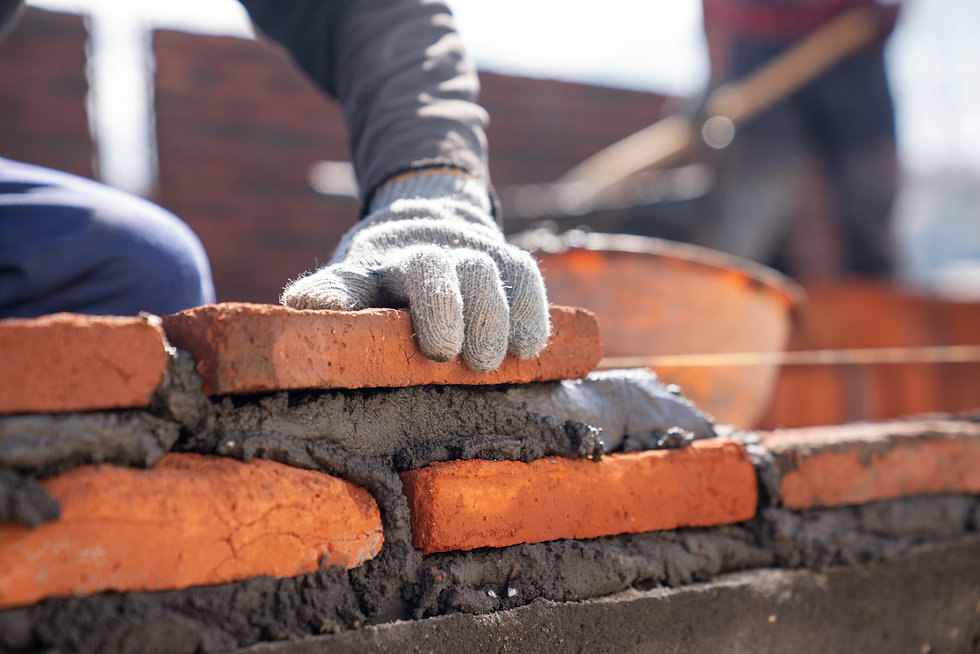 bricklayer-industrial-worker-installing-brick-masonry-with-trowel-putty-knife-construction