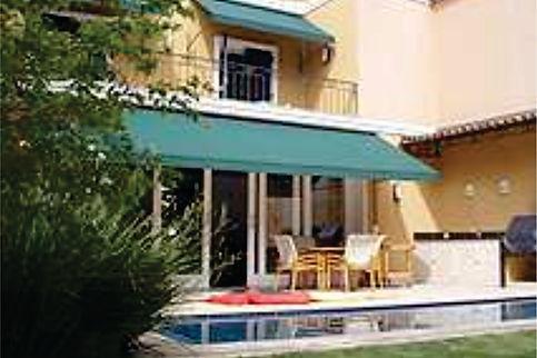 Casa vista da piscina e jardim, com área gourmet e varanda