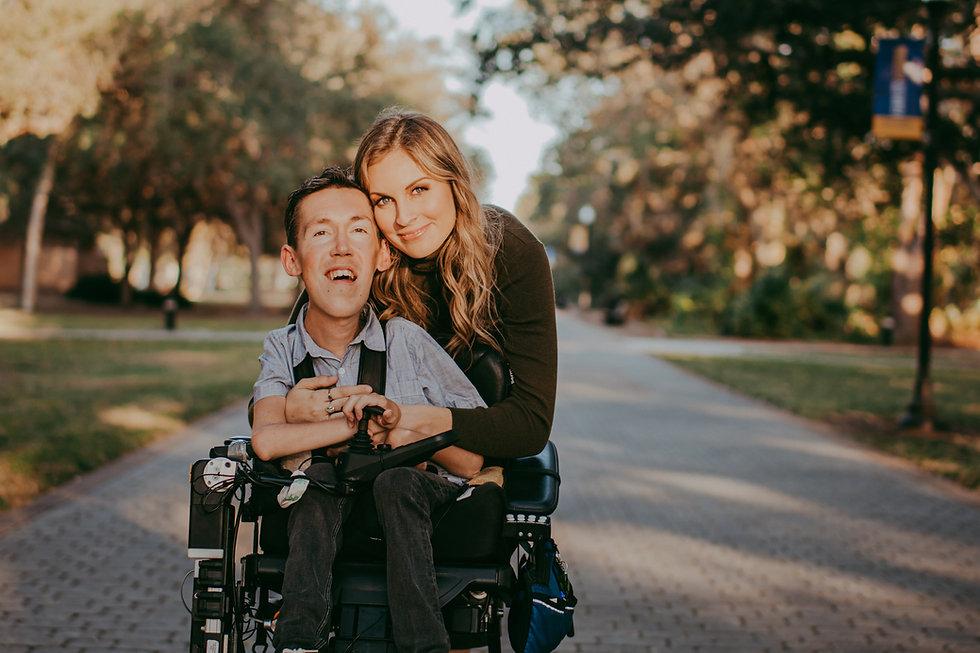 Hannah Aylward hugging Shane Burcaw in his wheelchair from behind
