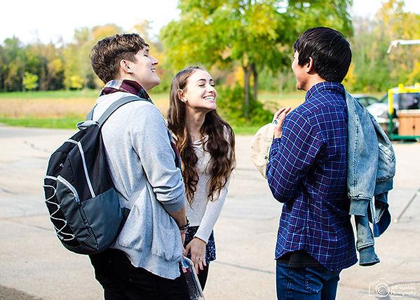 Billy Chengary, Lucía Rodriguez-Nelson, & Kento Matsunami laugh outside Oshkosh North High School
