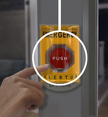 Hand pressing a wall mounted emergency m