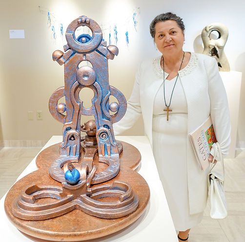 The artist Anne Furnaris photographed with her sculpture entitled the Gates of the Sun,