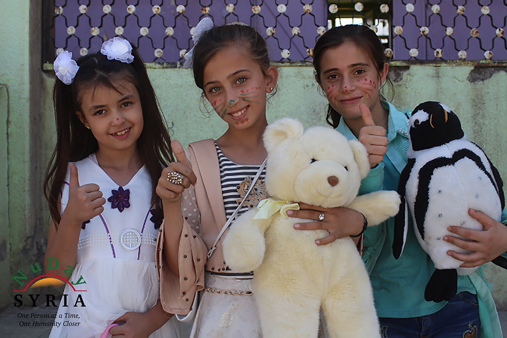 Three girls stand with their thumbs up. One of the girls is holding a stuffed bear; another is holding onto a stuffed penguin,