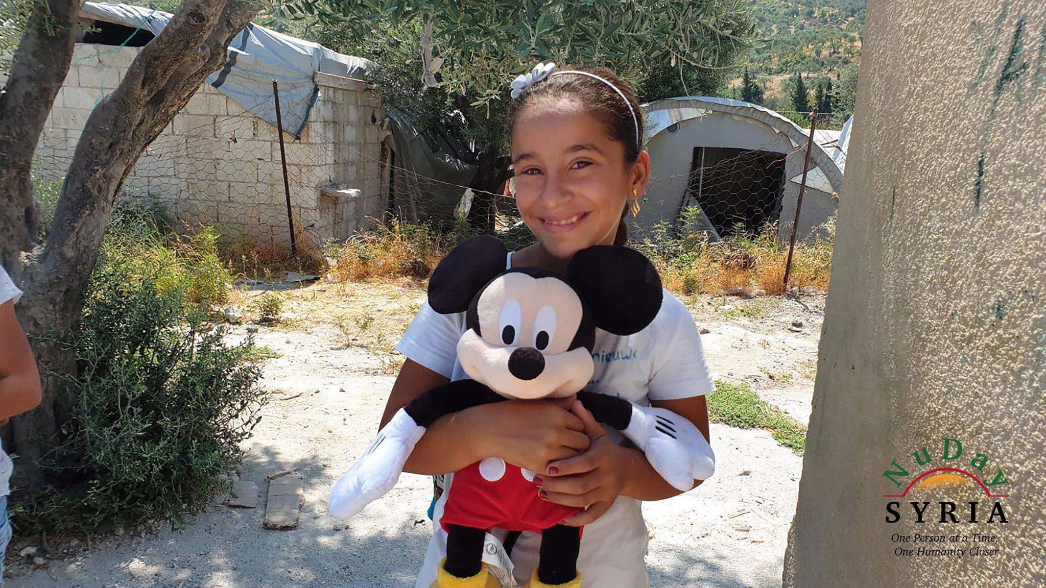 A ten year old girl hugs her Mickey Mouse teddy bear.