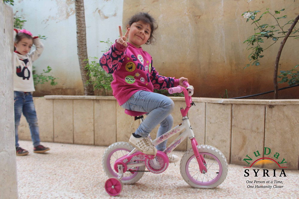 "A young girl dressed in a pink sweater with the word ""SMILE"" on it sits on a pink bike. The girl is smiling and holding her fingers into the peace sign."