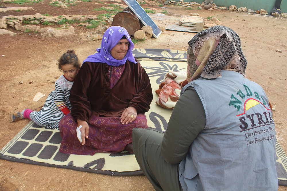 Syrian woman and child sit on a blanket in nature and speak with one of NuDay's female field staff.