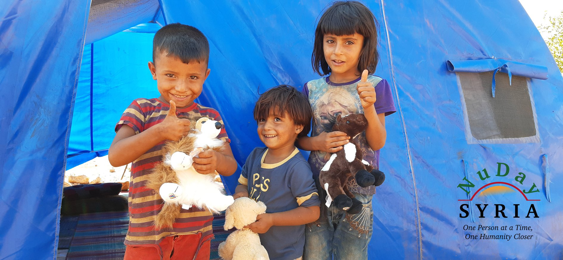 A boy in a red and brown striped shirt stands with his toddler brother (wearing a blue shirt) and older sister (in a purple Frozen tshirt) in front of a make-shift tent. All of the children are holding onto a stuffed animal.