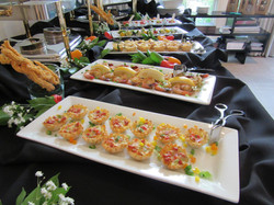 Appetizer party with Spanish frittatas and jumbo shrimp in foreground