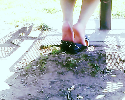 Shoeplay at the park. Bare feet and worn sweaty ballet flats