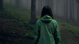 Back view of a young woman hiking in for