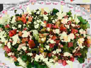 Tossed cucumbers and beets over bed of arugula with chevre on a china serving platter.