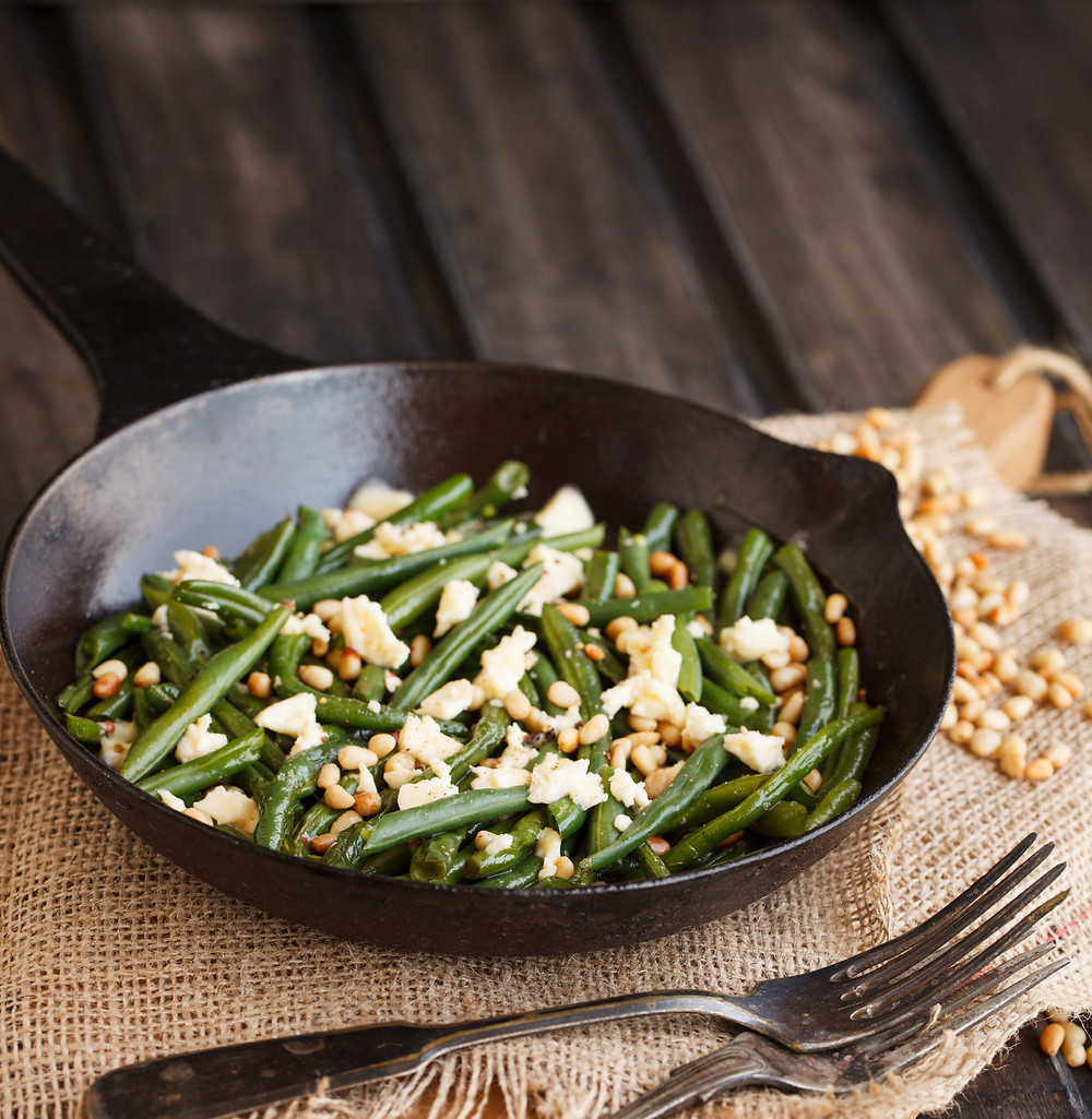 Green beans in a skillet with cheese and pine nuts