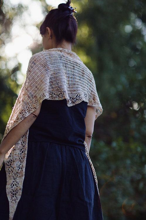 Back view of woman wearing diamond shaped shawlette. Handknit