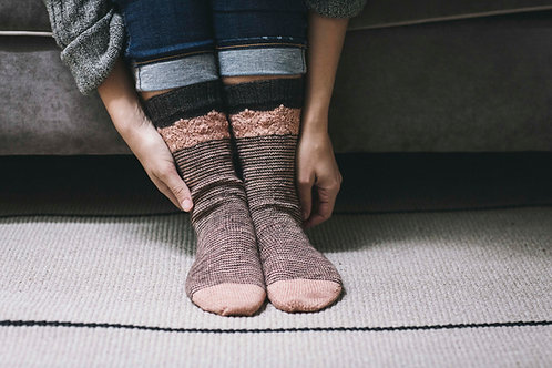 2 feet wearing hand-knit socks in pink and black. Hands reaching the ankles. The background is a gray velvet sofa.
